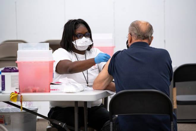 A health care worker administers a vaccine for COVID-19  recently at the Lake Square Mall in Leesburg. [Cindy Peterson/Correspondent]