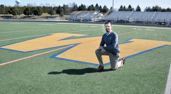 The new Wooster High School football coach Austin Holter by the large W on Follis Field.