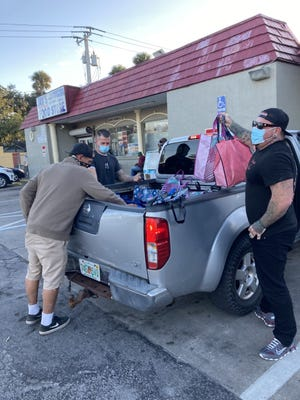 Street Team members unload the bed of a pickup truck, where they have stored reusable bags filled with the overdose-reversal drug naloxone and other harm reduction products.