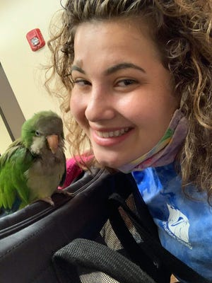 Madaline Delucco and her adopted parrot, Magic Bean.