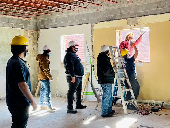 A construction manager (left) supervises high school students through Metro Community College as they get ready to install one of many new windows in what will be Englewood Arts Center, on Winner Road in Independence.