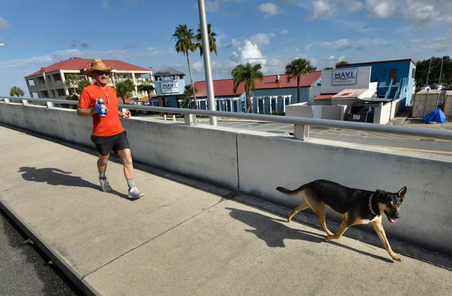 In July 2019 David Green trains with his dog, Lucky, on the Beach Boulevard bridge over the Intracoastal Waterway to prepare for an ultramarathon in the Colorado mountains.