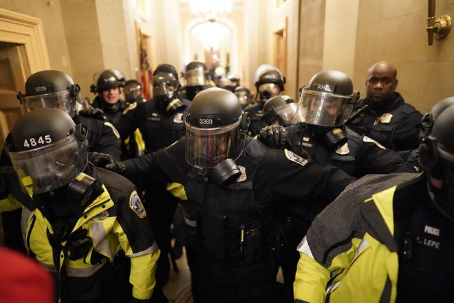 Riot police clear the hallway inside the Capitol on  Jan. 6, 2021, in Washington, D.C.