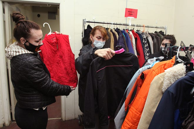 Shelly Benham, center, looks at clothing with her daughters Amber Watson, left, and Brittany Watson during a food, clothing and household item giveaway on Wednesday at The Salvation Army in Freeport.