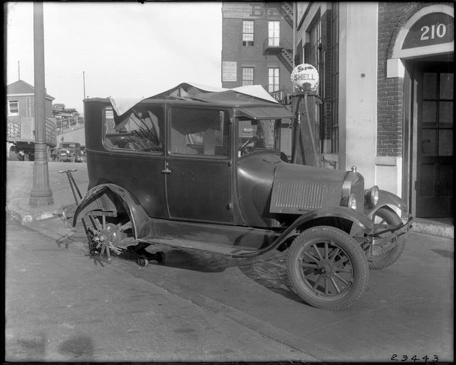 Traffic in Boston was not as bad in the early 1900s as it is today, but cars still had problems from time-to-time. This old wrecked car has a tire problem. Learn more from Digital Commonwealth at www.digitalcommonwealth.org.