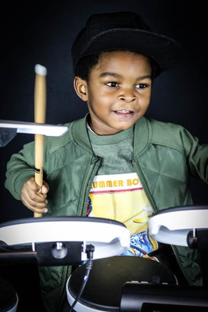 Drum student Tyree McMillian Jr., 3, prepares a song for the Zoom concert.