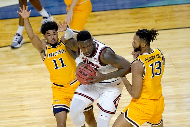 Illinois 's Kofi Cockburn, center, is pressured by Drexel's Camren Wynter (11) and Tim Perry Jr., during the first half of a first round NCAA college basketball tournament game Friday, March 19, 2021, at the Indiana Farmers Coliseum in Indianapolis .[AP Photo/Charles Rex Arbogast]