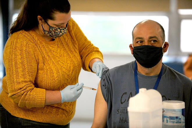 Andrew Benedetti, special education director at Framingham High School, receives a Moderna COVID-19 vaccine from Hemenway Elementary School nurse Aurelia Medina, March 18, 2021, at the Fuller Middle School vaccination clinic for school staff and teachers.