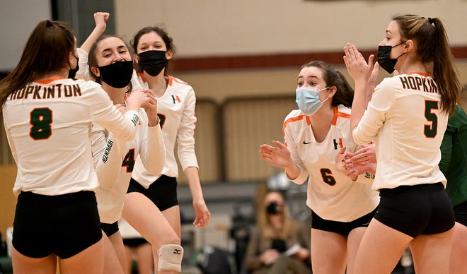 Hopkinton volleyball players celebrate a point during the first set  of a match against Ashland, at Hopkinton High School, March 18, 2021.