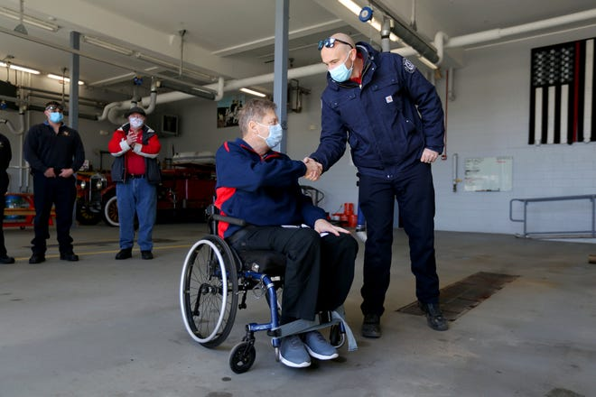 Seabrook resident Joseph Karpiak receives a check from the Hampton Firefighters Charity Organization on Friday afternoon at the Hampton Fire and Rescue Station after a tragic accident that left him paralyzed.
