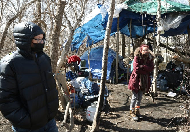 Tom Walsh and Cristal Ferreira took up residence in a tent city near the Seekonk River in Pawtucket months ago — on land where construction of a soccer stadium will soon begin.