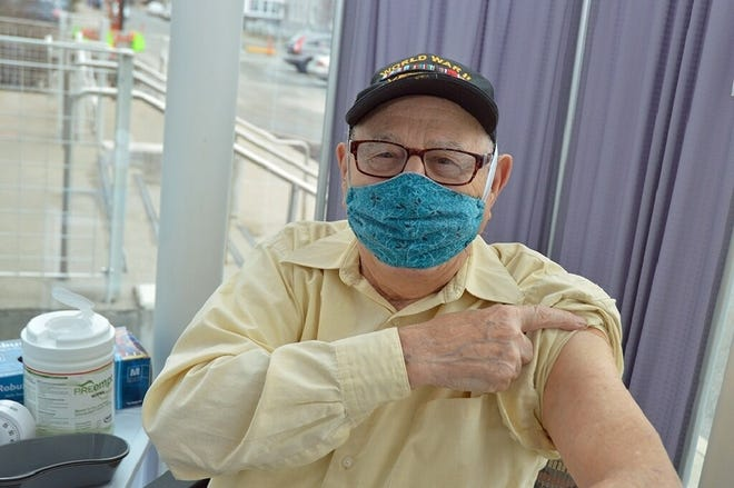 World War II Navy veteran Peter Ricci, 100, of West Warwick, points to his bandage after receiving his initial dose of the Moderna COVID-19 vaccine at the Providence VA Medical Center.