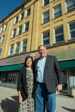 Riddle Block 9 new owners Doug Shelton and Melissa Zapanta Shelton tour the building with Main Street Ravenna executive director Julie McLain. Melissa Zapanta Shelton and Doug Shelton in front of the historic Ravenna building, recognizable for the yellow brick facade, that has apartments and store fronts, including the former Catholic Charities.