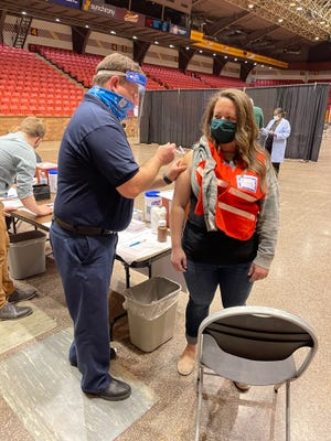 Abbey Kootz of Plain Township received her COVID-19 vaccine shot after volunteering with the Canton City Health Department, the same day as her husband serving about 6,000 miles away.