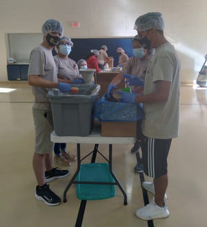 Volunteers and Rotarians pack meals to be distributed to families in need and the homeless in Manatee County on March 13.