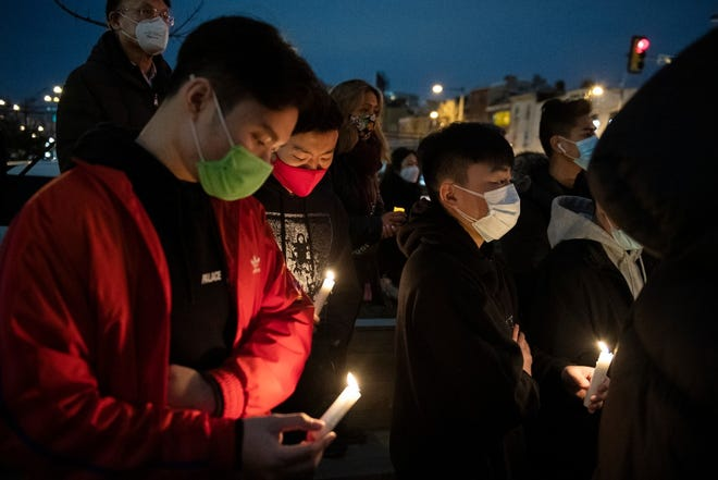 Community members gather for a vigil to mourn and confront the rising violence against Asian Americans at the 10th Street Plaza on Wednesday in Philadelphia. The vigil was held following a mass shooting in Atlanta that killed eight people, six of them women of Asian decent.