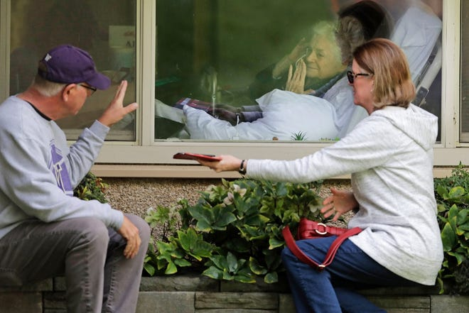 In this March 11, 2020, photo Judie Shape, center, who has tested positive for the coronavirus, blows a kiss to her son-in-law, Michael Spencer, left, as Shape's daughter, Lori Spencer, right, looks on, as they visit on the phone and look at each other through a window at the Life Care Center in Kirkland, Wash., near Seattle.