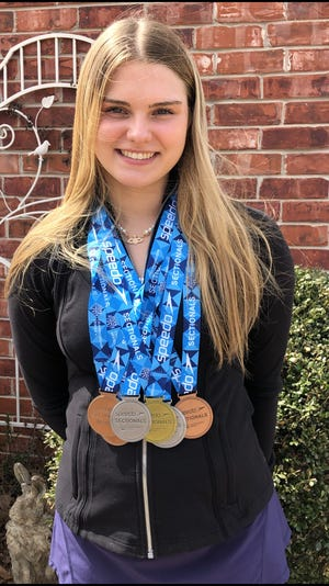 Piper McNeil poses with her medals.