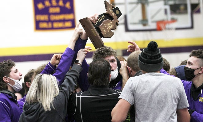 Justin Blankenship of Bronson raises the team district trophy following the Vikings' victory on Thursday.