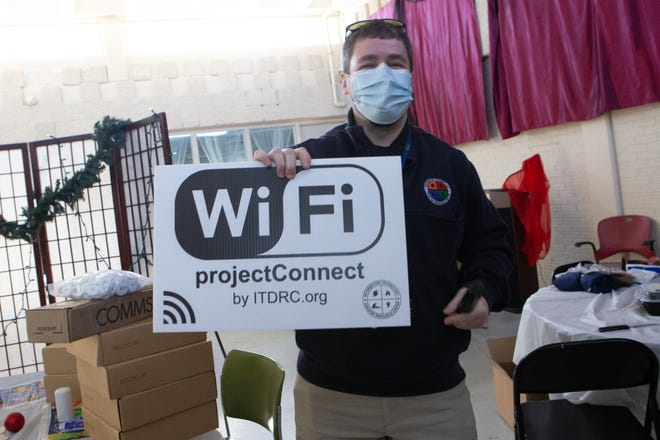 Jonathan Boyle, central division director for the Technology Disaster Resource Center, holds up a projectConnect sign while on site Friday morning at the Gil Carter Initiative, 2620 S.E. 23rd St. Volunteers with the resource center are helping stand up a wireless network at the facility to help residents in the area.