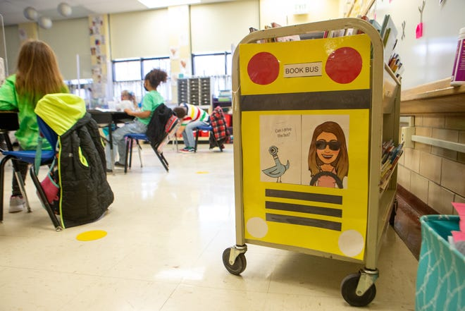 """A """"book bus"""" sits inside a classroom at Whitman Elementary School Wednesday morning as media specialist Alisha Schwinn reads to a class. For many students with access to them, books provided an escape during a year in which they were stuck at home. Not all were as lucky, though."""
