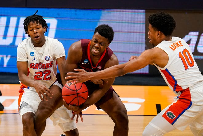 Virginia Tech guard Nahiem Alleyne (4), center, is trapped by Florida guards Tyree Appleby (22) and Noah Locke (10) in the second half of a first round game in the NCAA men's college basketball tournament at Hinkle Fieldhouse in Indianapolis, Friday, March 19, 2021. (AP Photo/Michael Conroy)