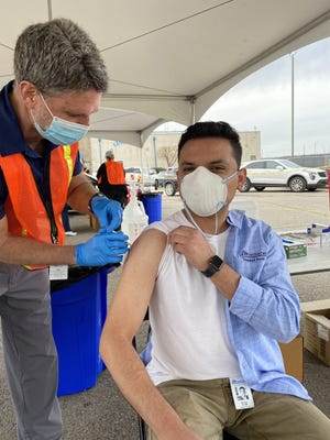 Nurse Supervisor Mark Karstetter gives Eli Ruiz his vaccine.