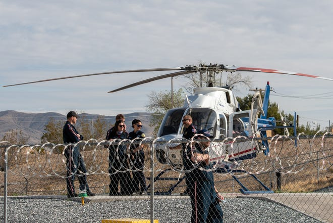 Crew members stand near a Mercy Air helicopter at the helipad near the former site of Barstow Community Hospital on Thursday, March 18, 2021.