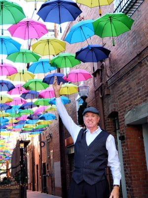John reaches to grab one of the floating umbrellas in Downtown Redlands.