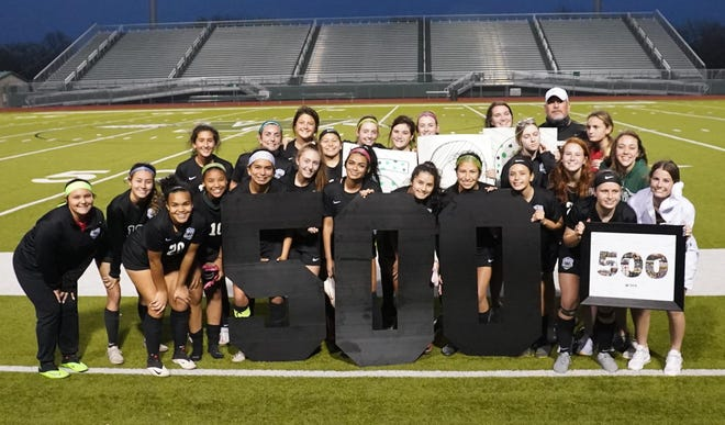 Waxahachie Lady Indians soccer team members gather on the pitch at Lumpkins Stadium for a celebration after head coach Jason Venable (back row, right) notched his 500th career coaching victory on Tuesday night in a 5-0 win over DeSoto.