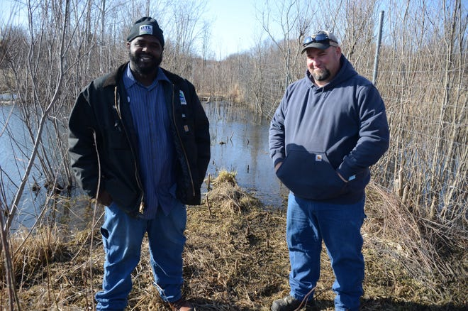 Jonathan Young, left, and Jim Tobias caught a dog at this pond Tuesday at the Battle Creek airport.  (Trace Christenson/The Enquirer)