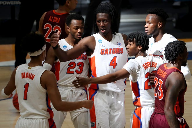 From left: Florida Gators guard Tre Mann (1), Florida Gators guard Scottie Lewis (23), Florida Gators forward Anthony Duruji (4), Florida Gators guard Tyree Appleby (22) and Florida Gators forward Keyontae Johnson (11) huddle in the first half during a first-round game of the 2021 NCAA Tournament against the Virginia Tech Hokies on Friday, March 19, 2021, at Hinkle Fieldhouse in Indianapolis, Ind.