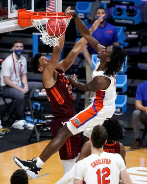 Florida Gators forward Anthony Duruji (4) dunks as Virginia Tech Hokies forward Keve Aluma (22) defends during the first round of the 2021 NCAA Tournament on Friday, March 19, 2021, at Hinkle Fieldhouse in Indianapolis, Ind.