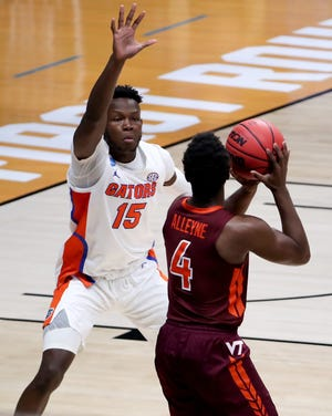 Virginia Tech Hokies guard Nahiem Alleyne (4) looks to pass as Florida Gators forward Osayi Osifo (15) defends in the first half during a first-round game of the 2021 NCAA Tournament on Friday, March 19, 2021, at Hinkle Fieldhouse in Indianapolis, Ind.