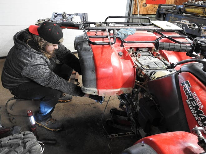 Hayden Davis works on a Honda Foreman four-wheeler at his new repair shop on Main Street in West Lafayette. The Fix on Main will replace Bates Car Care Center after 50 years in business. Hayden said he wants to work on anything with a motor.