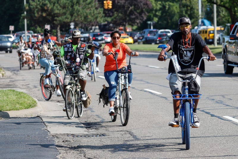 Jigga Caldwell of Detroit, far right, and his friends ride bicycles on Woodward Avenue near Birmingham during the Woodward Dream Cruise on August 19, 2017.