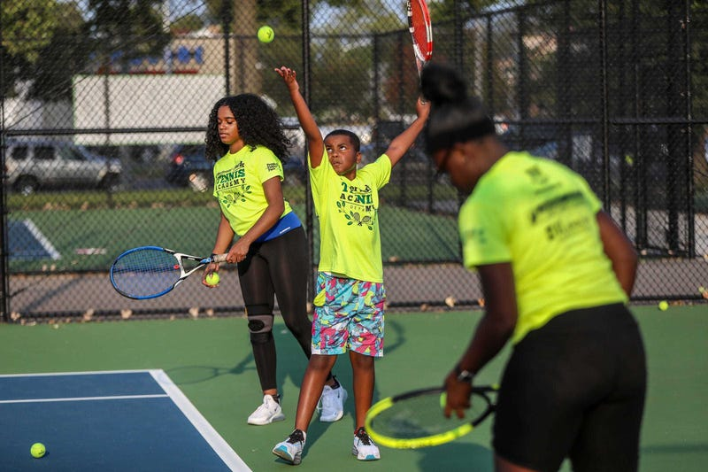 Kingyun Nelson, 10, of Detroit, tosses a tennis ball in the air while he practices his serve with his cousin Zoey McClanahan, 15, and other students, during the People of Palmer Park Junior Tennis Academy (PPTA) at Palmer Park in Detroit, on Sept. 23, 2020. PPTA, which gives tennis instruction to children age 7-16 years old is lead by Coach Leonora King and was recently awarded the 2020 Community Tennis Association of the Year by the United States Tennis Association. Nelson says he likes playing tennis because he gets to spend time with his family.