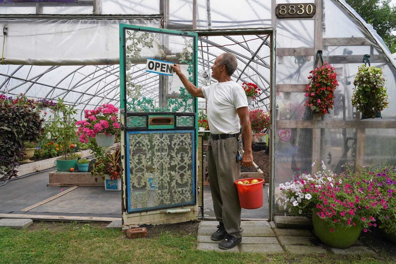 Bill Walton of Detroit changes his sign to read that his business is open while carrying a bucket of vegetables he harvested from one of his gardens while working in a neighborhood in Detroit's east side on Sept. 3, 2019.