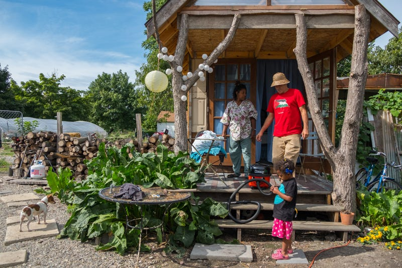 Greg Willerer, 49, and his wife Olivia Hubert, 33, and their daughter Wren Willerer, 4, stand outside on a cabin in their yard as they clean it up for guests coming in to stay for the night in Detroit's North Corktown neighborhood on Sept. 7, 2018.