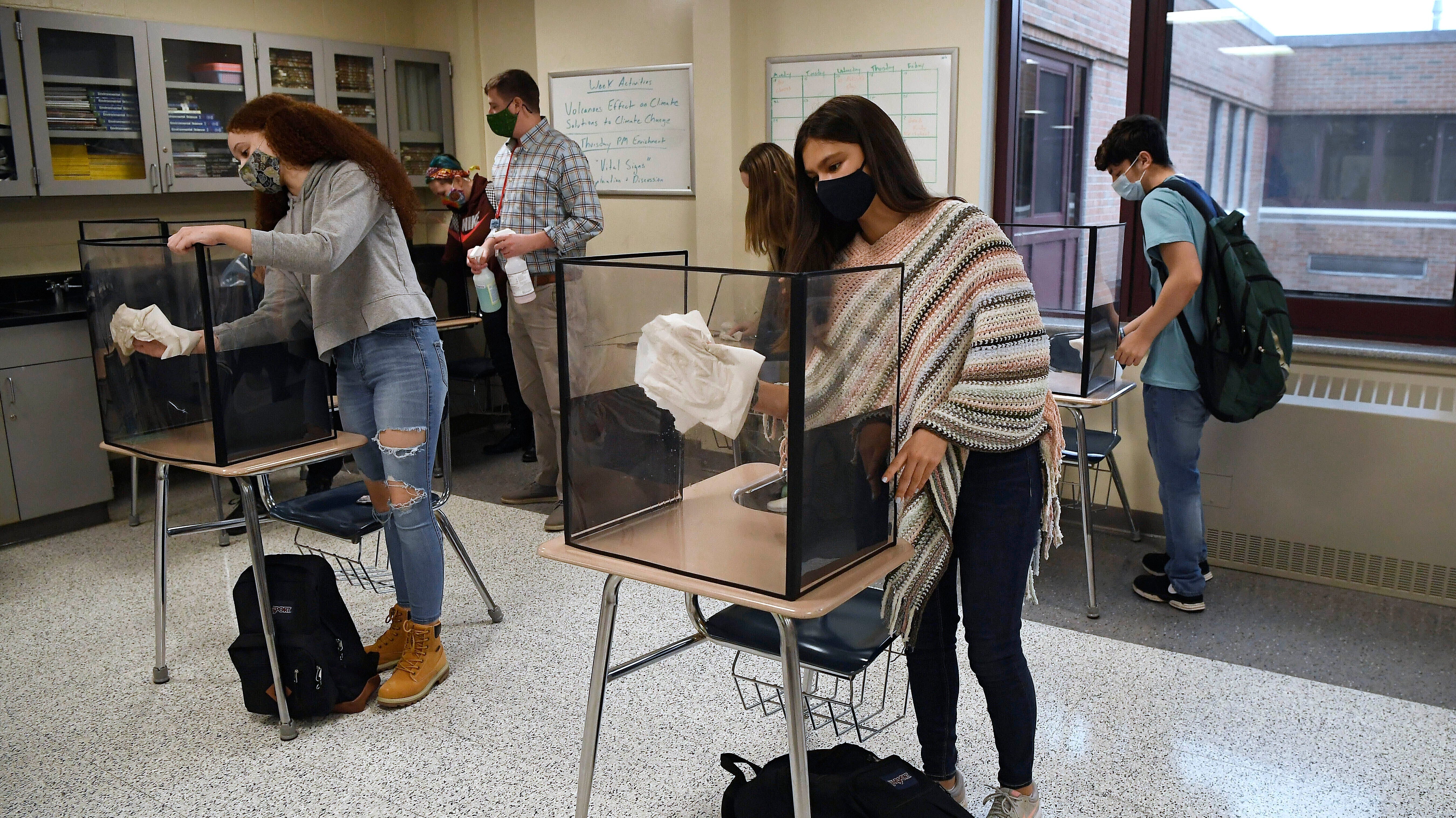 In this March 18, 2021, file photo, students in teacher Christopher Duggan's science class clean their work areas at the end of class at Windsor Locks High School in Windsor Locks, Conn.