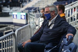 Indiana Governor Eric Holcomb, shown wearing a mask as he watches as Georgia Tech faces Loyola in the first round of NCAA March Madness on Friday, March 19, 2021, at Hinkle Fieldhouse in Indianapolis. Holcomb has announced his statewide mask mandate will end April 6.