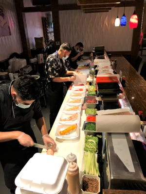 Asia Garden sushi chefs prepare meals in a process that has changed in the past year since COVID-19 arrived in West Tennessee.