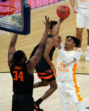 Mar 19, 2021; Indianapolis, Indiana, USA; Tennessee Volunteers guard Keon Johnson (45) shoots the ball over Oregon State Beavers forward Rodrigue Andela (34) during the second half in the first round of the 2021 NCAA Tournament at Bankers Life Fieldhouse. Mandatory Credit: Kirby Lee-USA TODAY Sports