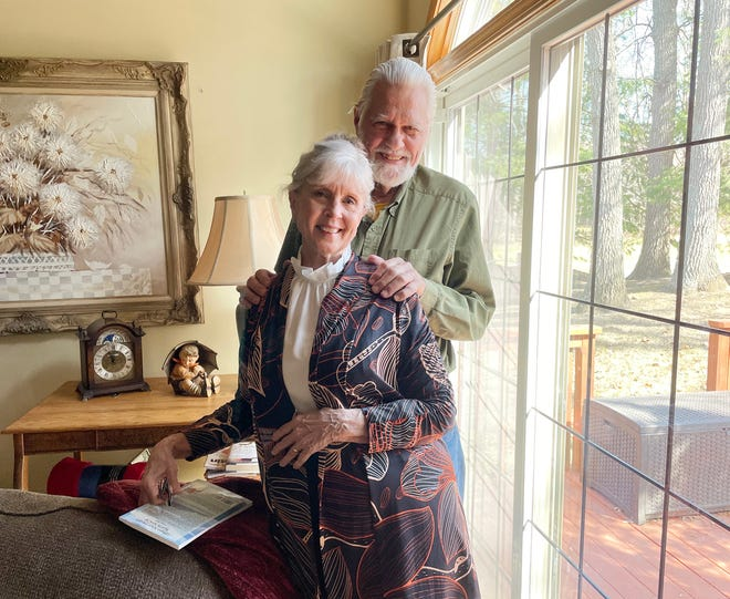 Brighton residents Kaye and Fred Karr pose for a photo in their home on March 19, 2021. Kaye just published her first novel this winter.