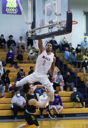 Male's Kaleb Glenn (1) attacks the basket against St. X's Chandler Strong (2) during the 26th District final at the Male High School in Louisville, Ky. on Mar. 18, 2021.  Male won 77-71.