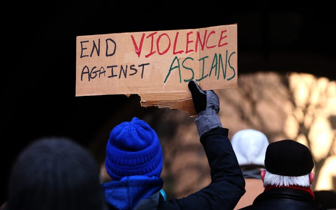 A rally participant holds a sign at the Standing Up Against Anti-Asian Violence Rally at Milwaukee City Hall. -  Several hundred turned out to speak about the unrest locally and nationally at the Standing Up Against Anti-Asian Violence Rally presented by the Asian American Pacific Islander (AAPI) Coalition of Wisconsin.