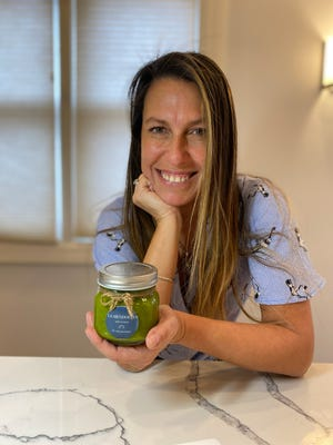 Marcela Lagos holds the chimichurri sauce she makes and sells with La Mendocina's empanadas.