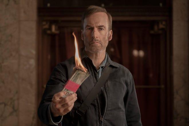 "Bob Odenkirk burns money as Hutch Mansell in ""Nobody,"" directed by Ilya Naishuller."