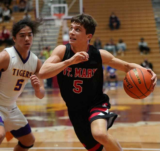 Dell Rapids St. Mary's Connor Libis charges past White River's Dylan Marshall on Thursday during the first round of the Class B state boys basketball tournament in Aberdeen.