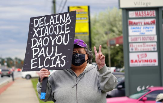 A woman attending a vigil to remember the victims of shootings at three Asian spas in the Atlanta area holds a sign with the names of the five victims.
